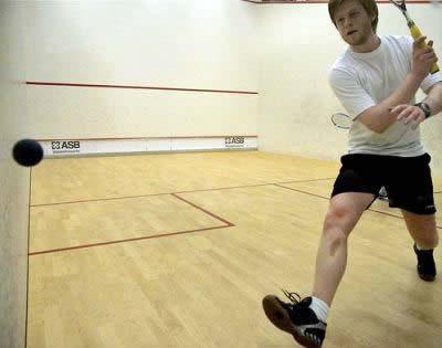squash rules player hitting a backhand